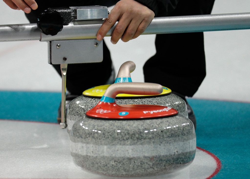 . An official measure the distance of the stones during the mixed doubles curling match between Norway and China at the 2018 Winter Olympics in Gangneung, South Korea, Sunday, Feb. 11, 2018. Norway won. (AP Photo/Aaron Favila)
