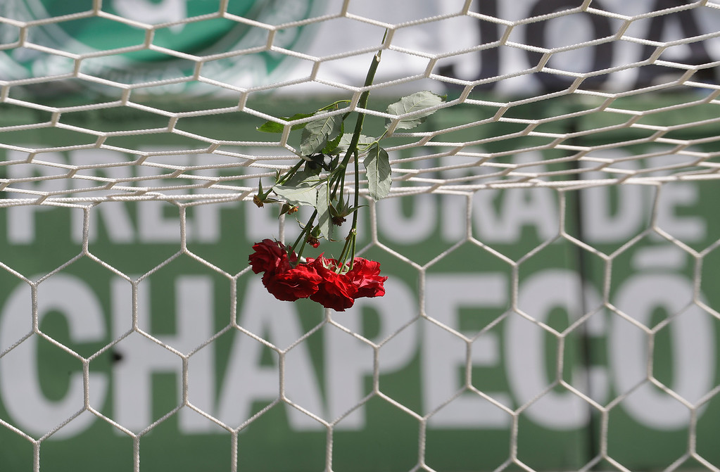 . Flowers hang from a soccer net at the Arena Conda stadium in Chapeco, Brazil, Tuesday, Nov. 29, 2016. A chartered plane that was carrying the Brazilian soccer team Chapecoense to the biggest match of its history crashed into a Colombian hillside and broke into pieces, Colombian officials said Tuesday. (AP Photo/Andre Penner)