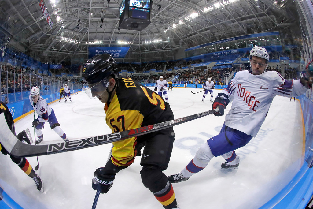 . Marcel Goc (57), of Germany, and Mattias Norstebo (10), of Norway, battle for the puck during the second period of the preliminary round of the men\'s hockey game at the 2018 Winter Olympics in Gangneung, South Korea, Sunday, Feb. 18, 2018. (AP Photo/Julio Cortez)