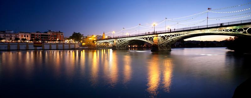 Triana bridge and Betis street at dusk with decorative lighting for La Vela festival, Seville, Spain