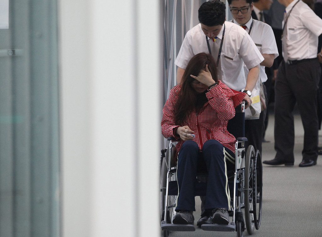 ". A passenger who was on the crashed Asiana Airline\'s aircraft, is helped upon her arrival at Incheon Airport on July 8, 2013, in Incheon, South Korea. The pilot of the crashed Asiana plane at San Francisco airport was still ""in training\"" for the Boeing 777 when he attempted to land the aircraft under supervision on Saturday, the South Korean airline said.  (Kim Hong-Ji-Pool/Getty Images)"
