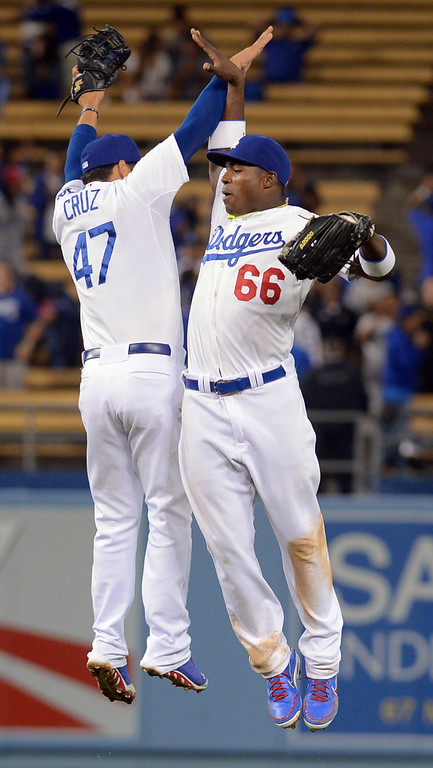 . New Dodger Yasiel Puig celebrates with Luis Cruz after Puig completed a double play to end the game against the Padres June 3, 2013 in Los Angeles, CA.  The Dodgers won the game 2-1.(Andy Holzman/Staff Photographer)
