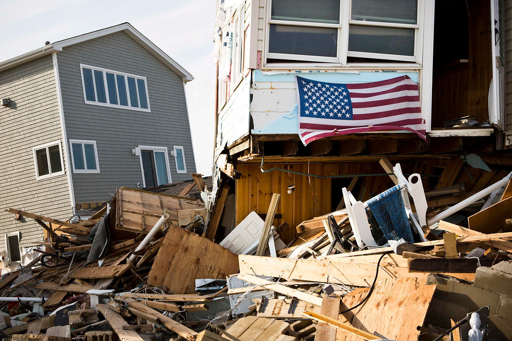 . A U.S. flag hangs from a home that was damaged by Hurricane Sandy, in the Ortley Beach area of Toms River, New Jersey November 28, 2012. The storm made landfall along the New Jersey coastline on October 29, 2012 - one month ago tomorrow. REUTERS/Andrew Burton