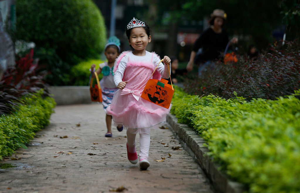 . A child celebrates Halloween by parading through her neighborhood collecting candies from local shops in Taipei, Taiwan, Thursday, Oct. 31, 2013. (AP Photo/Wally Santana)