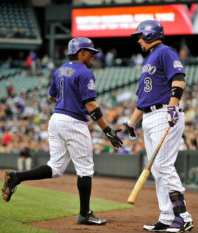 . Colorado Rockies\' Eric Young Jr. (1) is congratulated by Michael Cuddyer (3) after scoring a run against the Tampa Bay Rays during the first inning of a baseball game Saturday, May 4, 2013, in Denver. (AP Photo/Jack Dempsey)