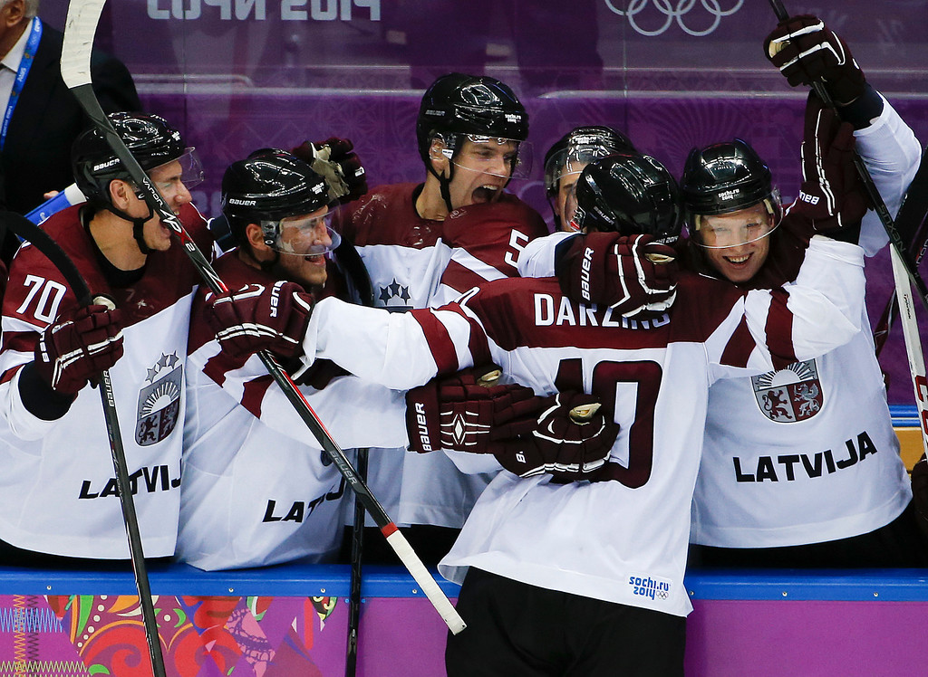 . Latvia forward Lauris Darzins is congratulated by teammates after scoring against Switzerland in the third period of a men\'s ice hockey game at the 2014 Winter Olympics, Tuesday, Feb. 18, 2014, in Sochi, Russia. Latvia won 3-1 to advance to the quarterfinals. (AP Photo/Julio Cortez)