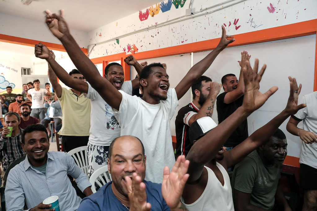 . Migrants supporting the French national soccer team celebrate as they watch on a TV set the final soccer match between Croatia and France during the Russia 2018 soccer World Cup, at Ritsona camp, northeast of Athens, Sunday, July 15, 2018. (AP Photo/Yorgos Karahalis)