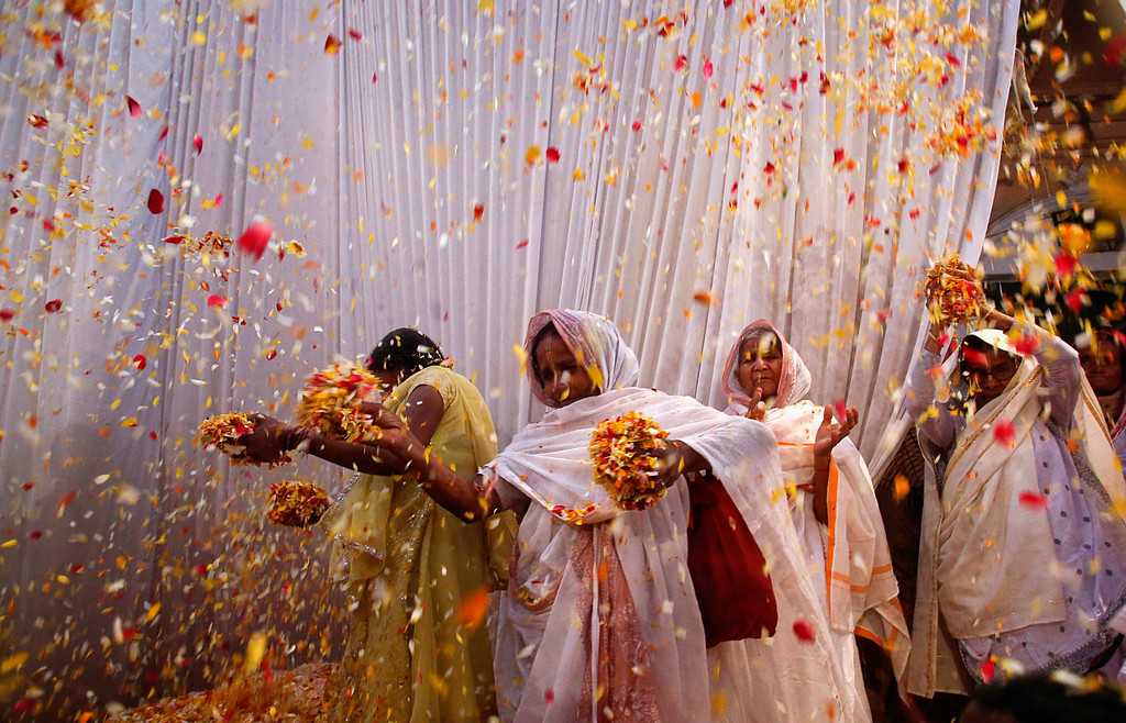 . Widows throw flowers into the air during a holi celebration at the Meera Sahavagini ashram in Vrindavan in the northern Indian state of Uttar Pradesh March 24, 2013. Traditionally in Hindu culture, widows are expected to renounce earthly pleasure so they do not celebrate holi, but for the first time, women at the shelter for widows who have been abandoned by their families celebrated the festival by throwing flowers and coloured powder. Holi, also known as the Festival of Colours, heralds the beginning of spring and is celebrated all over India. REUTERS/Vivek Prakash