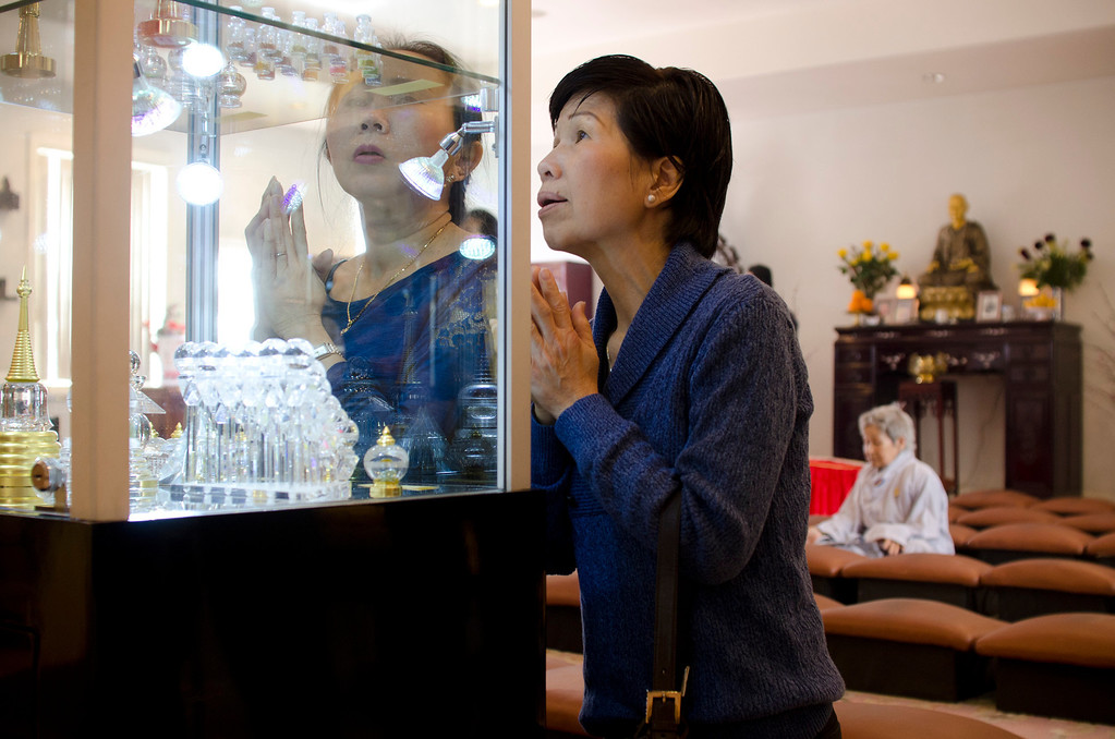 . Nhu Dang, left, and Dieu Nhien, right, of Santa Ana kneel to look at the different relics on display at Lu Mountain Temple in Rosemead, Calif., Sunday, March 31, 2013. Several shariras were made available for viewing to the public including a rare Shakyamuni Buddha tooth relic measuring about two inches in height. (SGVN/Correspondent photo by Anibal Ortiz)