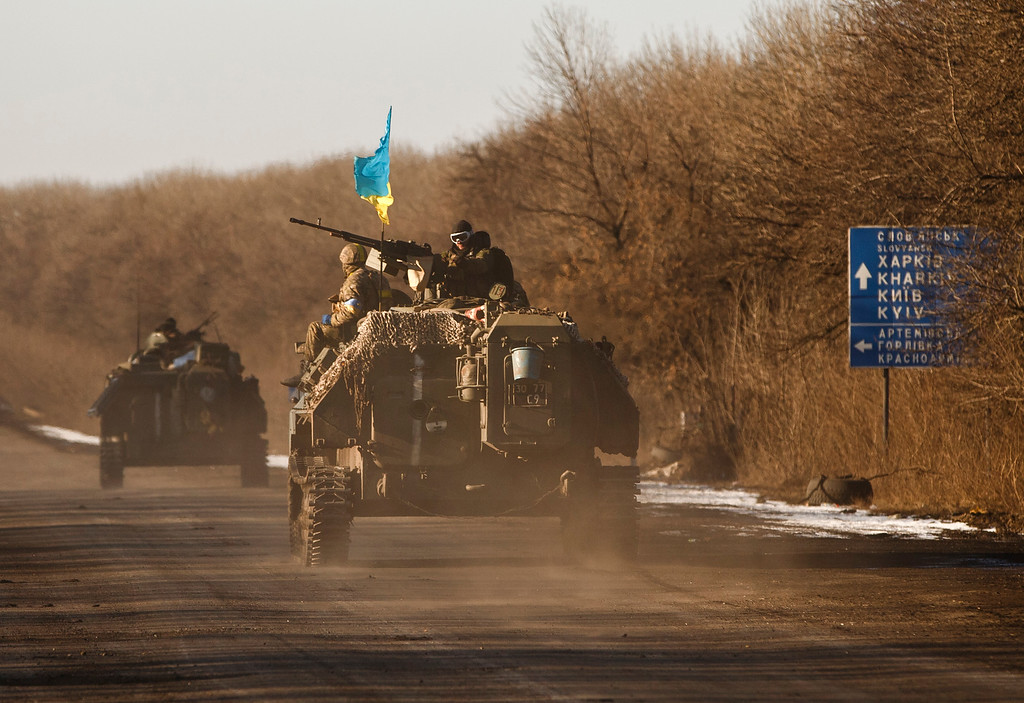 . Ukrainian troops ride on an armored vehicle outside Artemivsk, Ukraine, while pulling out of Debaltseve, Wednesday, Feb. 18, 2015. After weeks of relentless fighting, the embattled Ukrainian rail hub of Debaltseve fell Wednesday to Russia-backed separatists, who hoisted a flag in triumph over the town. The Ukrainian president confirmed that he had ordered troops to pull out and the rebels reported taking hundreds of soldiers captive. (AP Photo/Vadim Ghirda)