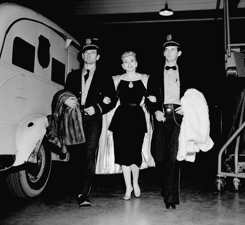 ". Zsa Zsa Gabor is escorted by two Brinks guards as she arrives at CBS\' Television City in Hollywood on Dec. 1, 1955, with three fur coats valued at $100,000 and wearing a million dollars worth of jewelry.   She was preparing for rehearsals for the ""Climax\"" TV show, in which she wears all the expensive adornments.   On her dress is a 100-carat golden yellow diamond, the \""Shah of Persia,\"" valued at $950,000, by its owners.  Brinks guards are Merle Plumb (left) and Robert Padgett.      (AP Photo/Harold Filan)"