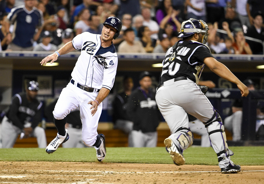 . SAN DIEGO, CA - AUGUST 12:  Tommy Medica #14 of the San Diego Padres scores ahead of the throw to Wilin Rosario #20 of the Colorado Rockies during the eighth inning of a baseball game at Petco Park August, 12, 2014 in San Diego, California.  (Photo by Denis Poroy/Getty Images)