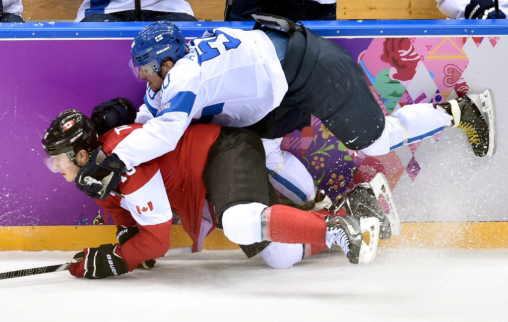 . Finland\'s Juhamatti Aaltonen, top, takes down Canada\'s Jonathan Toews during the second period of a men\'s ice hockey game at the Winter Olympics, Sunday, Feb. 16, 2014, in Sochi, Russia. (AP Photo/The Canadian Press, Nathan Denette)