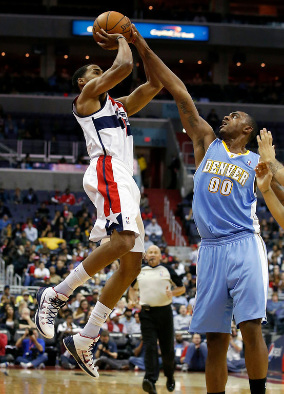 . Washington Wizards guard Garrett Temple (17) tries to shoot over Denver Nuggets forward Darrell Arthur (00) in the first half of an NBA basketball game on Monday, Dec. 9, 2013, in Washington. The Nuggets won 75-74. (AP Photo/Alex Brandon)