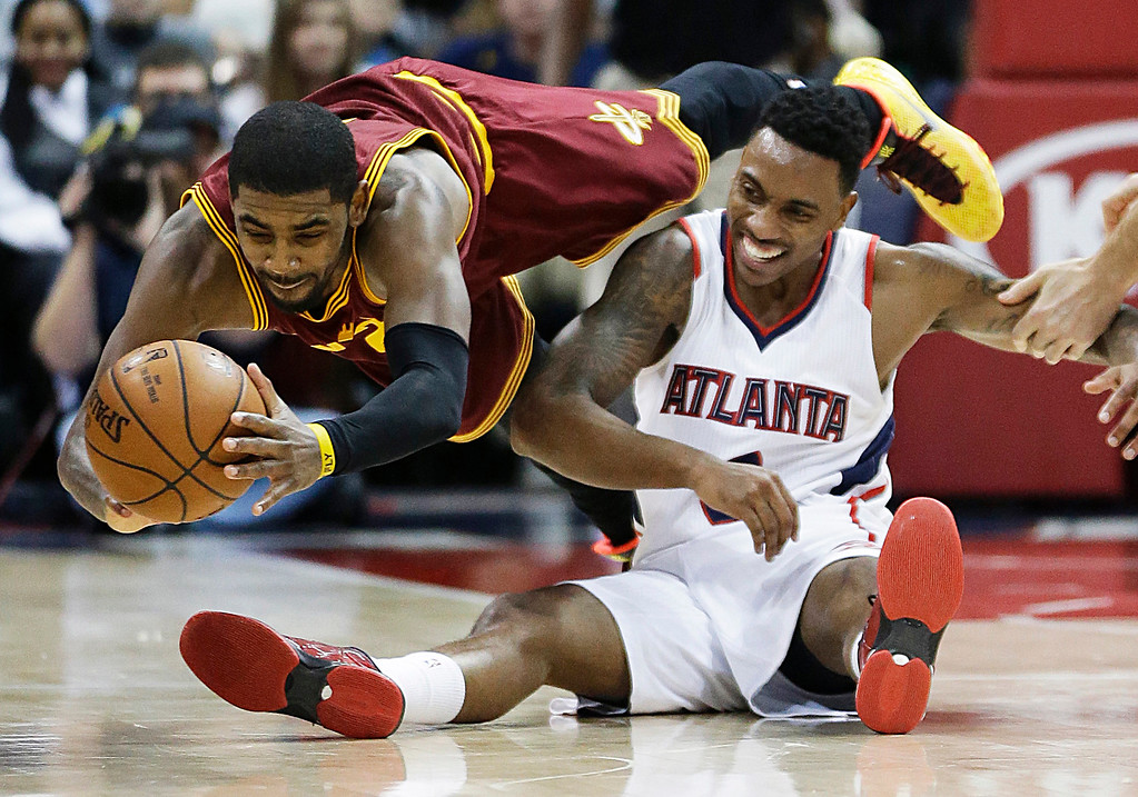. Cleveland Cavaliers\' Kyrie Irving, left, dives for a loose ball against Atlanta Hawks\' Jeff Teague in the fourth quarter of an NBA basketball game, Tuesday, Dec. 30, 2014, in Atlanta. (AP Photo/David Goldman)
