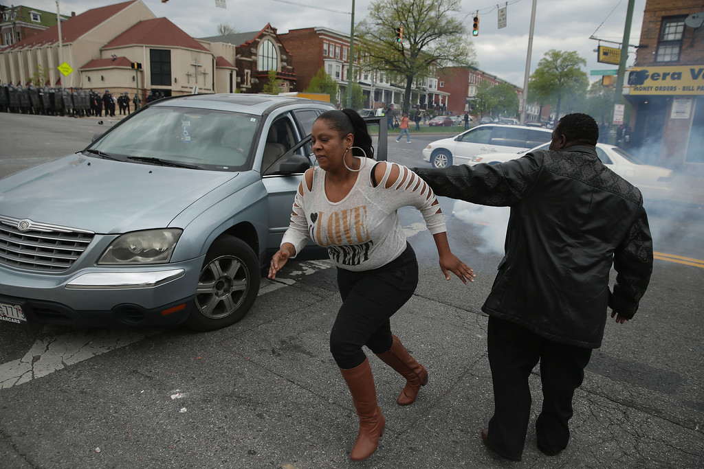 . BALTIMORE, MD - APRIL 27:  A woman abandons her car in the middle of an intersection as Baltimore Police officers clash with violent protesters outside the Mondawmin Mall following the funeral of Freddie Gray April 27, 2015 in Baltimore, Maryland. Gray, 25, who was arrested for possessing a switch blade knife April 12 outside the Gilmor Homes housing project on Baltimore\'s west side. According to his attorney, Gray died a week later in the hospital from a severe spinal cord injury he received while in police custody.  (Photo by Chip Somodevilla/Getty Images)