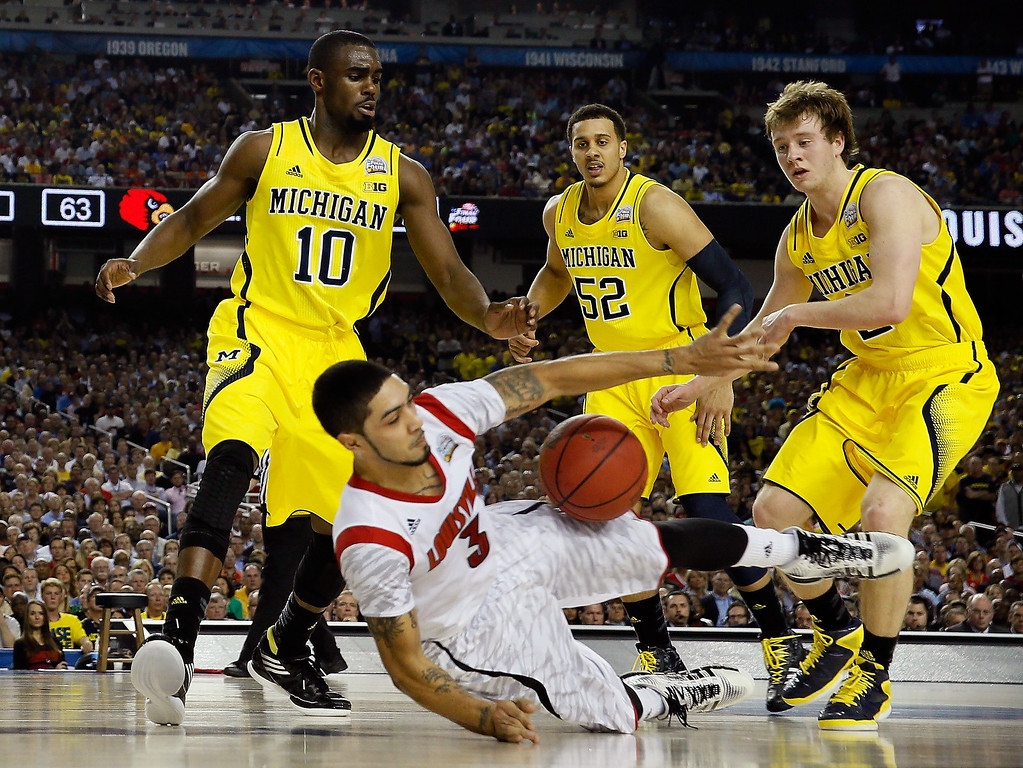 . Peyton Siva #3 of the Louisville Cardinals attempts to control the ball in the second half as he falls down against Tim Hardaway Jr. #10, Jordan Morgan #52 and Spike Albrecht #2 of the Michigan Wolverines during the 2013 NCAA Men\'s Final Four Championship at the Georgia Dome on April 8, 2013 in Atlanta, Georgia.  (Photo by Streeter Lecka/Getty Images)