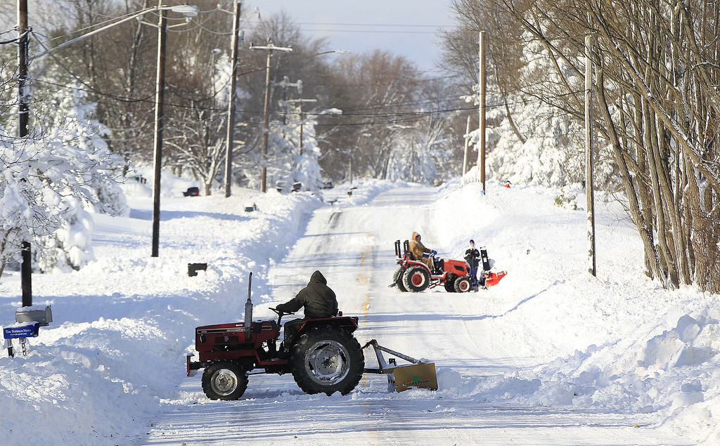 . Tractors clear snow along Powers Road in Orchard Park, N.Y.  on Wednesday, Nov. 19, 2014.  A ferocious lake-effect storm left the Buffalo area buried under 6 feet of snow Wednesday, trapping people on highways and in homes, and another storm expected to drop 2 to 3 feet more was on its way. (AP Photo/The Buffalo News, Harry Scull Jr.)