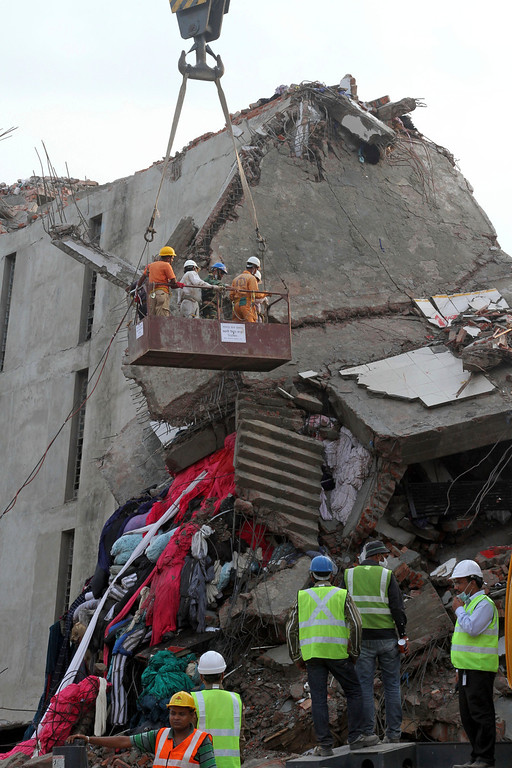 . Bangladeshi authorities use machinery lift search teams as they clear the broken and crushed concrete slabs of a building that collapsed in Savar, outskirts of Dhaka, Bangladesh, Tuesday, April 30, 2013. (AP Photo/Palash Khan)