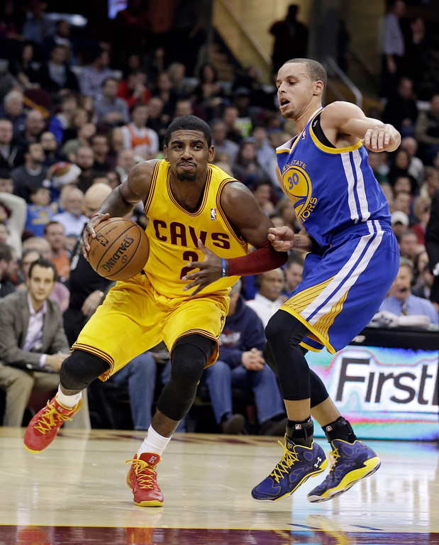 . Cleveland Cavaliers\' Kyrie Irving tries to get past Golden State Warriors\' Stephen Curry, right, during the second quarter of an NBA basketball game Sunday, Dec. 29, 2013, in Cleveland. (AP Photo/Tony Dejak)