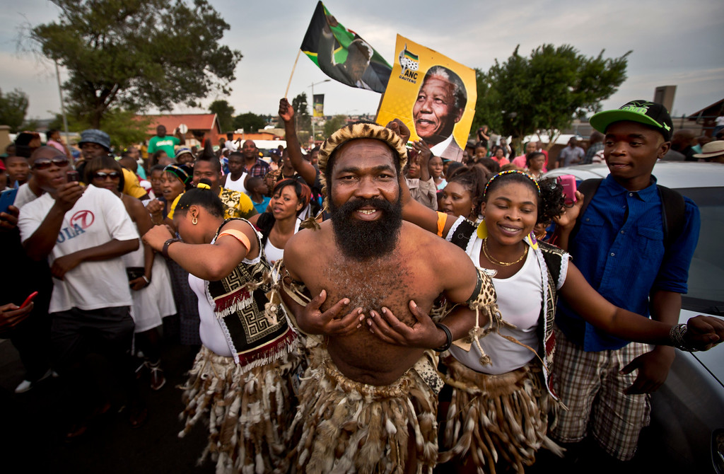 . A troupe of traditional dancers in the street entertain mourners who have come to pay their respects at Nelson Mandela\'s old house, in Soweto, Johannesburg, South Africa Saturday, Dec. 7, 2013. (AP Photo/Ben Curtis)