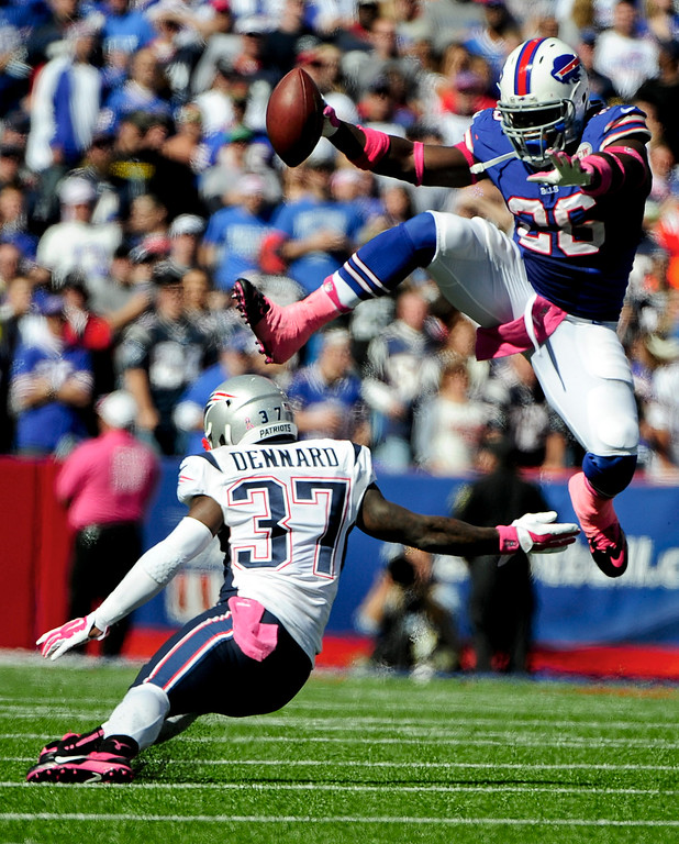 . Buffalo Bills running back Anthony Dixon (26) hurdles New England Patriots cornerback Alfonzo Dennard (37) during the first half of an NFL football game Sunday, Oct. 12, 2014, in Orchard Park, N.Y. (AP Photo/Gary Wiepert)
