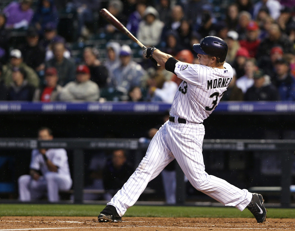 . Colorado Rockies\' Justin Morneau follows through with his swing after connecting for a two-run home run against the Philadelphia Phillies in the fourth inning of a baseball game in Denver on Saturday, April 19, 2014. (AP Photo/David Zalubowski)