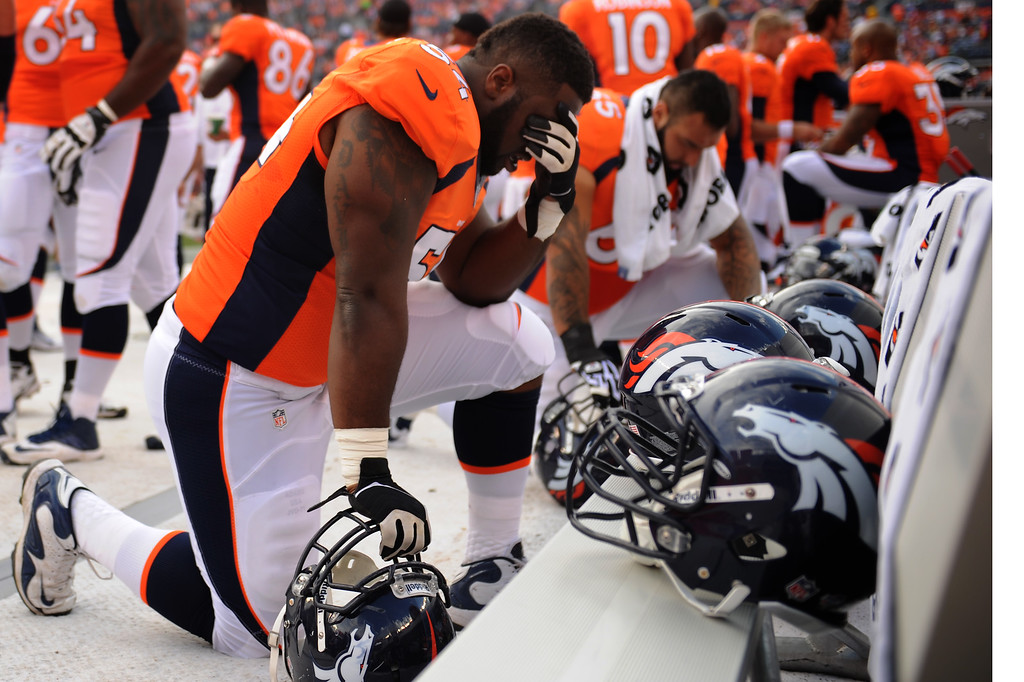 . DENVER, CO. - August 24: Guard C.J. Davis (54) of the Denver Broncos prays before his game vs the St. Louis Rams during the 3rd pre-season game of the season at Sports Authority Field at Mile High. August 24, 2013 Denver, Colorado. (Photo By Joe Amon/The Denver Post)
