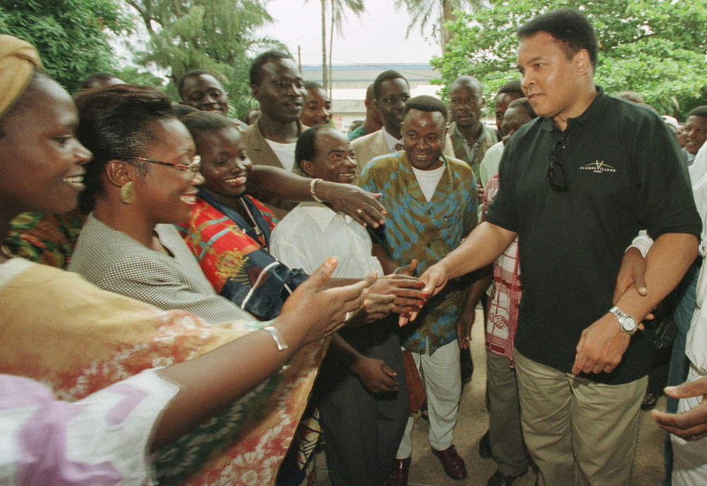 Description of . Former heavyweight boxing champion Muhammad Ali shakes hands with fans in Abidjan, Ivory Coast Tuesday, Aug. 19, 1997 outside the Ministry of Sports offices. Ali is on a goodwill visit to West Africa delivering food to 400 orphans in San Pedro, Ivory Coast along the Liberian border where tens of thousands of refugees who fled Liberia's civil war are living. The plight of the orphans came to Ali's attention when a nun caring for the children wrote a letter asking for his help. (AP Photo/David Guttenfelder)