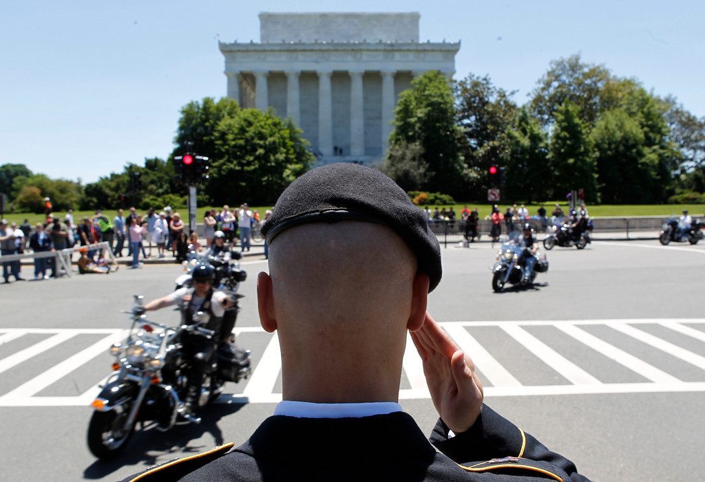". Motorcycles drive past the Lincoln Memorial as Colin Morris, of the US Army, salutes during the annual Rolling Thunder ""Ride for Freedom\"" parade ahead of Memorial Day in Washington, Sunday, May 26, 2013. (AP Photo/Molly Riley)"
