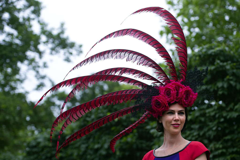 . A race-goer wearing a flamboyant hat poses for photographers during Ladies Day at the annual Royal Ascot horse racing event near Windsor, Berkshire on June 19, 2014. AFP PHOTO / CARL COURT/AFP/Getty Images
