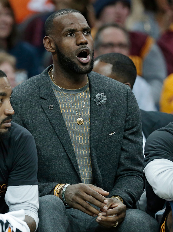 . Cleveland Cavaliers\' LeBron James watches from the bench in the first half of an NBA basketball game against the Toronto Raptors, Wednesday, April 12, 2017, in Cleveland. (AP Photo/Tony Dejak)