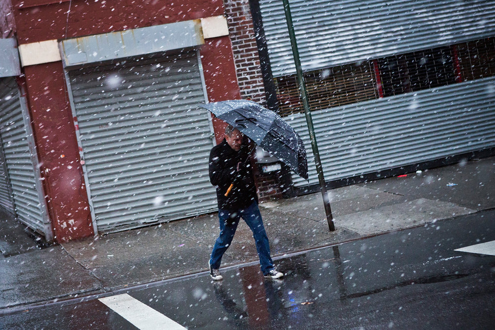 Description of . A man uses an umbrella to protect himself from winter snow on December 26, 2012 in New York City. Snow, mixed with and changing to rain, is expected to hit the New York City area this afternoon into the evening. (Photo by Andrew Burton/Getty Images)