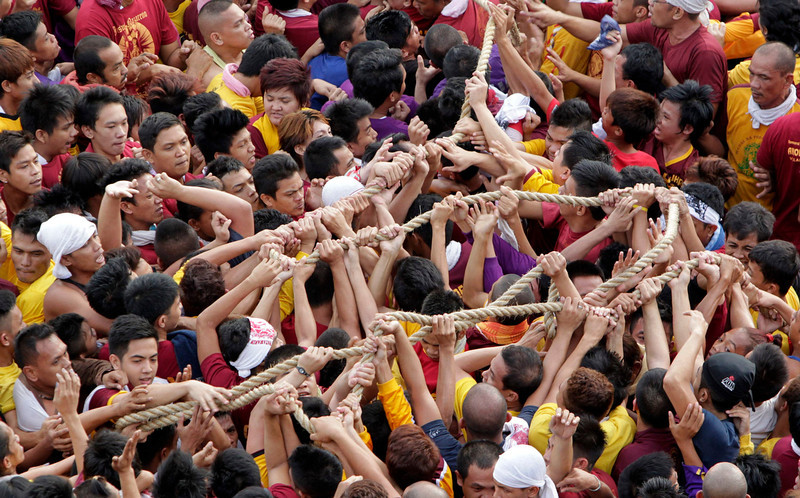 . Devotees hold on to the rope that pulls the carriage bearing the statue of the Black Nazarene (not pictured) during a procession in Manila January 9, 2013. The Black Nazarene, a life-size wooden statue of Jesus Christ carved in Mexico and brought to the Philippines in the 17th century, is believed to have healing powers in the predominantly Roman Catholic country. It is paraded through the narrow streets of Manila\'s old city from dawn to midnight. Police said about 500,000 people joined the procession on Wednesday.  REUTERS/Erik De Castro