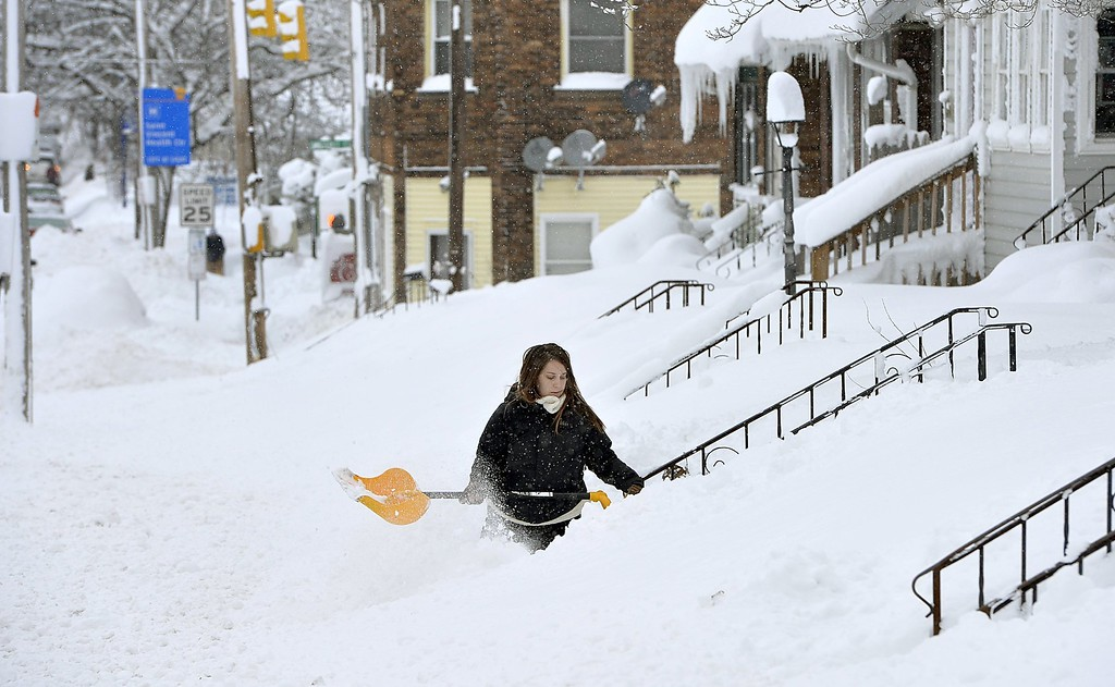 . Rochelle Carlotti, 28, shovels steps near her home after a record snowfall on Tuesday, Dec. 26, 2017, in Erie, Pa. The National Weather Service office in Cleveland says Monday\'s storm brought 34 inches of snow, an all-time daily snowfall record for Erie. (Greg Wohlford/Erie Times-News via AP)