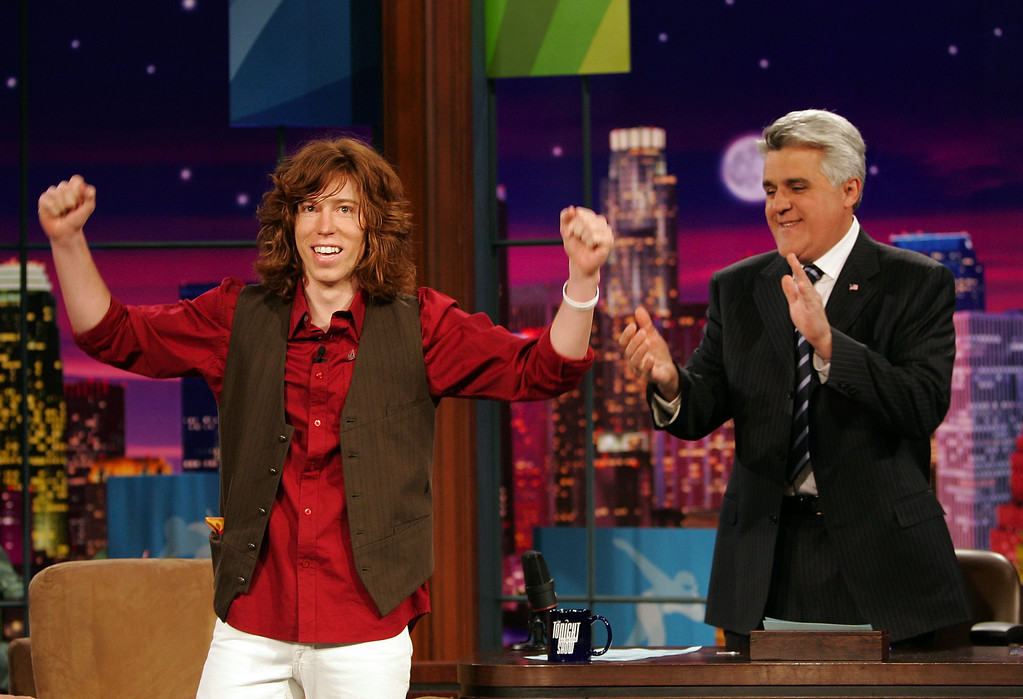 ". Snowboarder Shaun White, also known and ""The Flying Tomato,\"" who wan a gold medal in the Men\'s Halfpipe Snowboard competition at the Turin 2006 Winter Olympic Games acknowledges the audience as Tonight Show host Jay Leno looks on, Thursday, Feb. 16, 2006, in Burbank Calif. (AP Photo/Mark J. Terrill)"