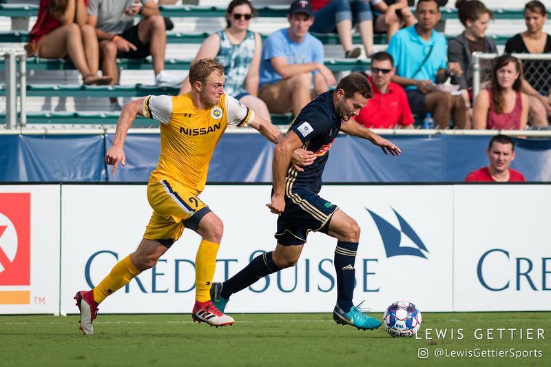 Nashville SC midfielder Matt LaGrassa (20) and North Carolina FC defender Steven Miller (31)