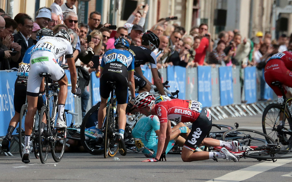 . Belgium\'s Jurgen van den Broeck, in red with race number 131, crashes during the seventh stage of the Tour de France cycling race over 234.5 kilometers (145.7 miles) with start in Epernay and finish in Nancy, France, Friday, July 11, 2014. (AP Photo/Fred Mons, Pool)