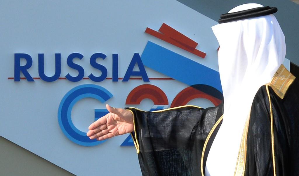 . Saudi Arabia\'s Minister of Finance Ibrahim bin Abdulaziz Al-Assaf prepares to shake hands with Russian President at the start of the G20 summit on September 5, 2013 in Saint Petersburg.      AFP PHOTO / YURI KADOBNOV/AFP/Getty Images