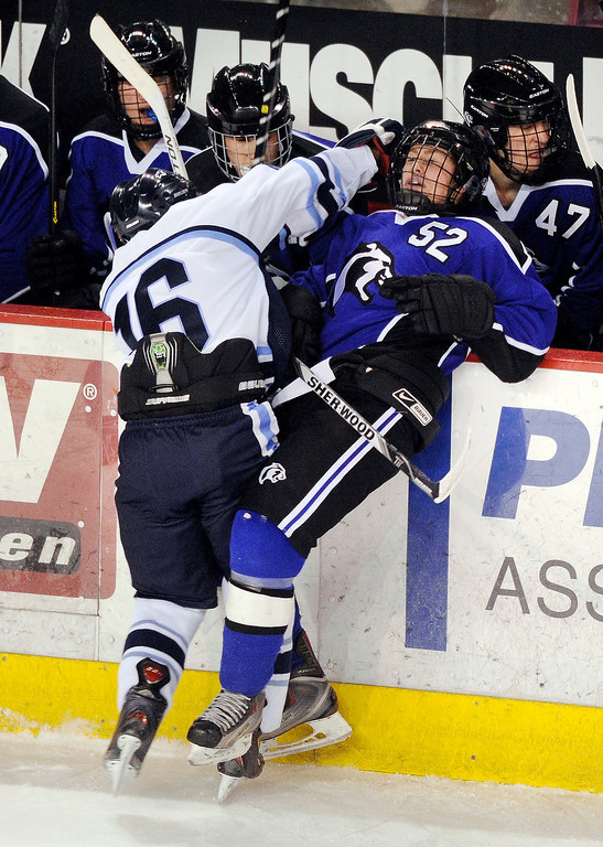. DENVER, CO. - FEBRUARY 28: Mustangs forward Kyle Valdez (16) put Cougars forward Tad Strohauer (52) back into his own bench on a check in the first period. Ralston Valley High School took on Resurrection Christian Thursday night, February 28, 2013 in a semifinal match in the Colorado State Ice Hockey Championships at Magness Arena in Denver. (Photo By Karl Gehring/The Denver Post)