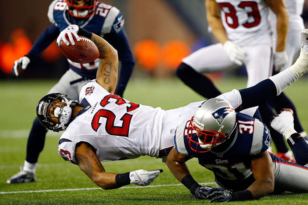 Description of . Arian Foster #23 of the Houston Texans stretches for a first down against Aqib Talib #31 of the New England Patriots during the 2013 AFC Divisional Playoffs game at Gillette Stadium on January 13, 2013 in Foxboro, Massachusetts.  (Photo by Jared Wickerham/Getty Images)