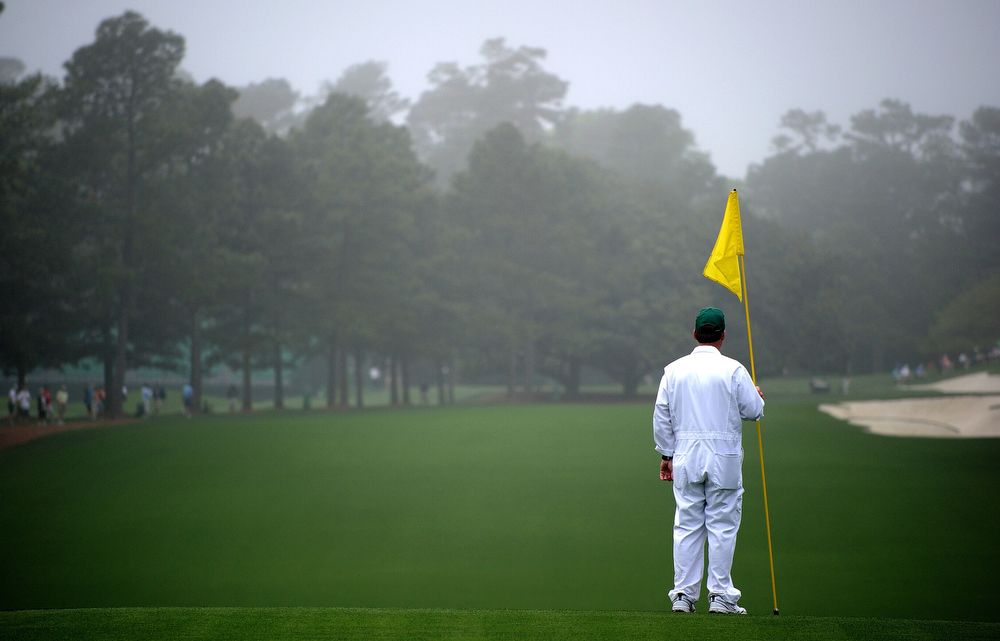 Description of . A caddie is seen on the first hole before the start of the first round of the 2013 Masters Tournament at Augusta National Golf Club on April 11, 2013 in Augusta, Georgia.  (Photo by Harry How/Getty Images)