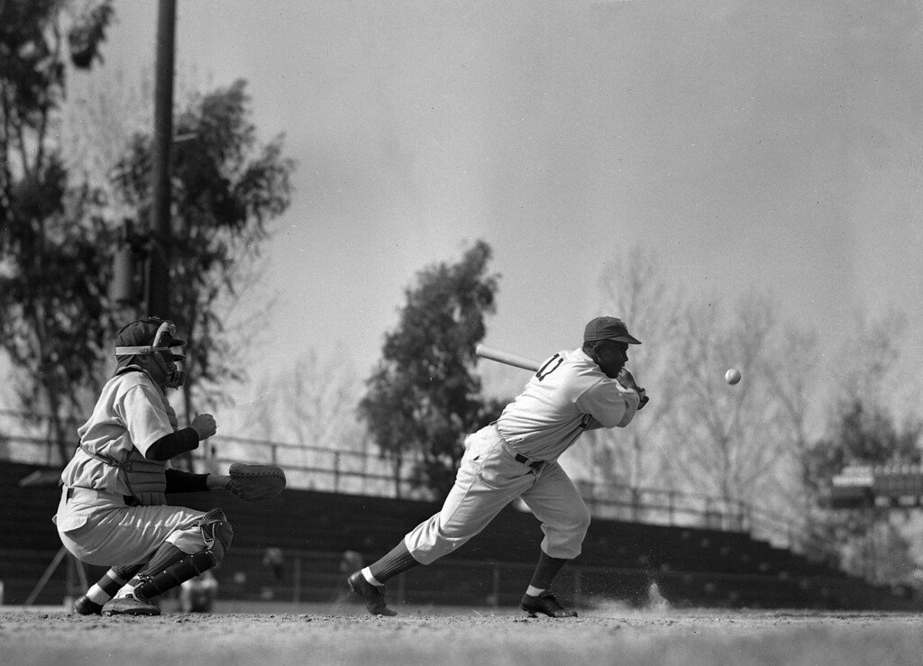 . Jackie Robinson swings and hits during a scene in the film of his career, Feb. 20, 1950, in Anaheim, California.  (AP Photo/Frank Filan)