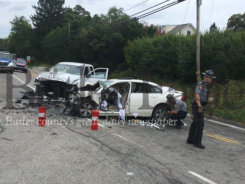 Two state police officers investigate a two-vehicle crash on Route 68 that left both drivers seriously injured in Summit Township.