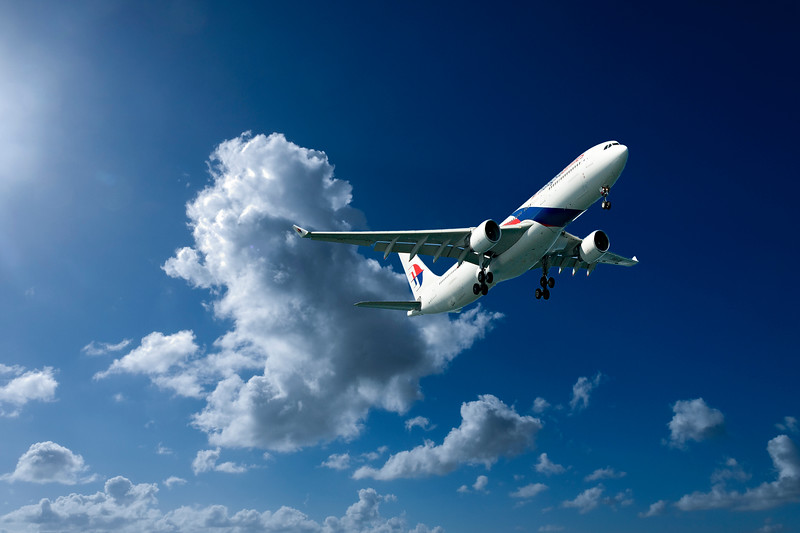 Aircraft in flight with cumulonimbus cloud in blue sky. Australia.