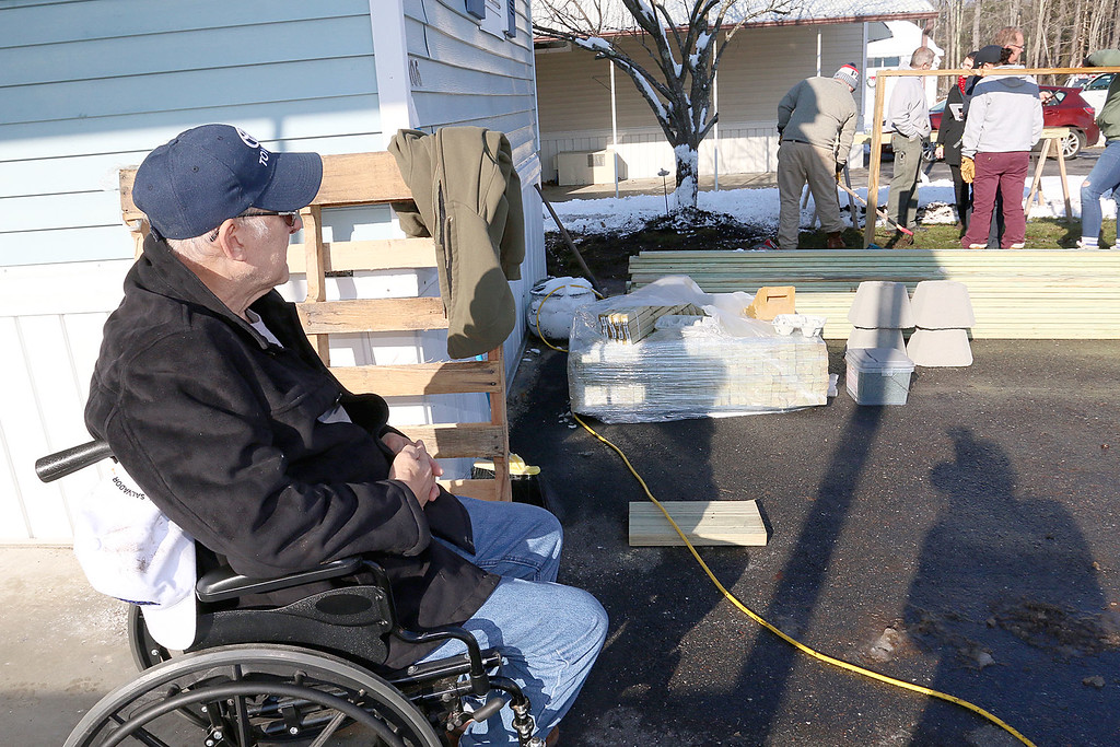 . Navy Veteran Seaman Donald Denoncourt, 77, watches as the 20 or so firefighters clean up the wood from his driveway as they where told they could not build a handicap ramp for him at his home in the Meadowbrook Acres mobile home park on Central Street in Leominster.  SENTINEL & ENTERPRISE/JOHN LOVE