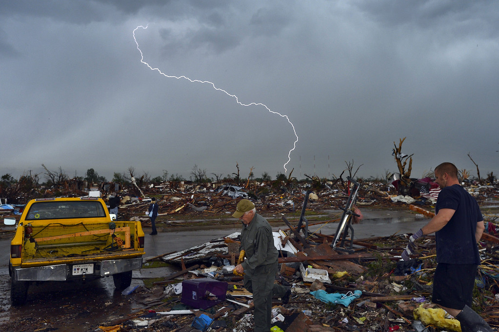 . Lightning strikes during a thunder storm as tornado survivors search for salvagable stuffs at their devastated home on May 23, 2013, in Moore, Oklahoma. Severe thunderstorms barreled through this Oklahoma City suburb at dawn Thursday, complicating clean-up efforts three days after a powerful tornado killed 24 people and destroyed 2,400 homes. More rain was forecast to fall on Moore, soaking the disaster zone where residents had just the day before, under clear blue skies, started picking through the rubble of their destroyed houses to recover personal effects. JEWEL SAMAD/AFP/Getty Images