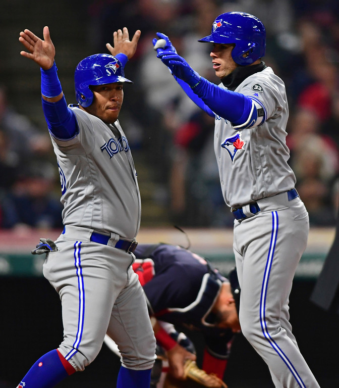 . Toronto Blue Jays\' Aledmys Diaz, right, is congratulated by Yangervis Solarte after hitting a three-run home run off Cleveland Indians starting pitcher Mike Clevnger during the fourth inning of a baseball game Friday, April 13, 2018, in Cleveland. (AP Photo/David Dermer)