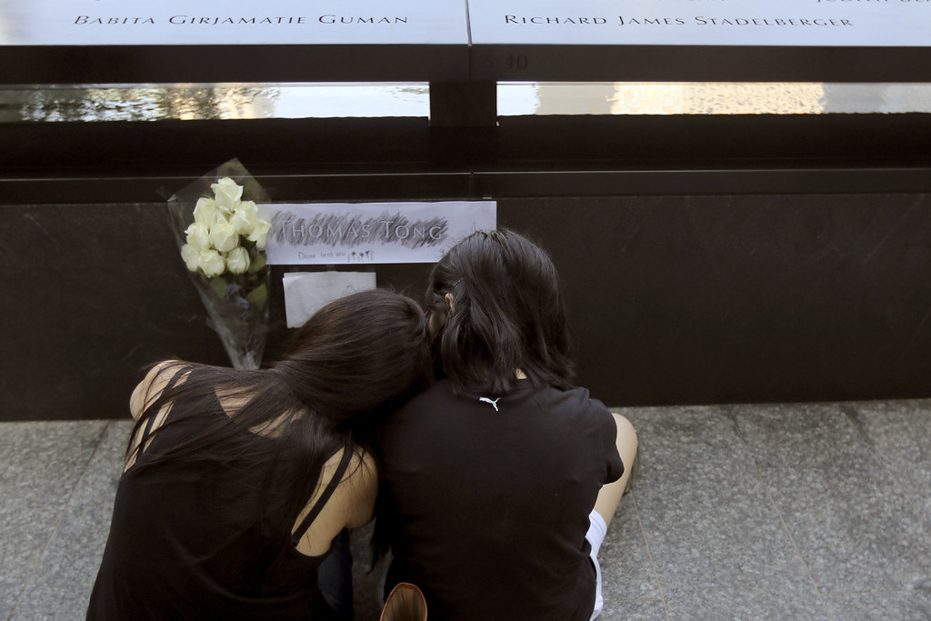 . Elena, left, and Elissa Tong mourn their husband and father Thomas Tong at the South Pool of the 9/11 Memorial during ceremonies for the twelfth anniversary of the terrorist attacks on lower Manhattan at the World Trade Center site on September 11, 2013 in New York City.  (Photo by Mary Altaffer-Pool/Getty Images)