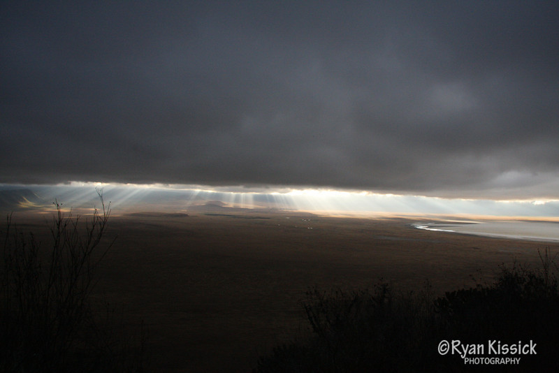 Early morning sunbeams peak through the clouds in Tanzania's Ngorogoro Crater